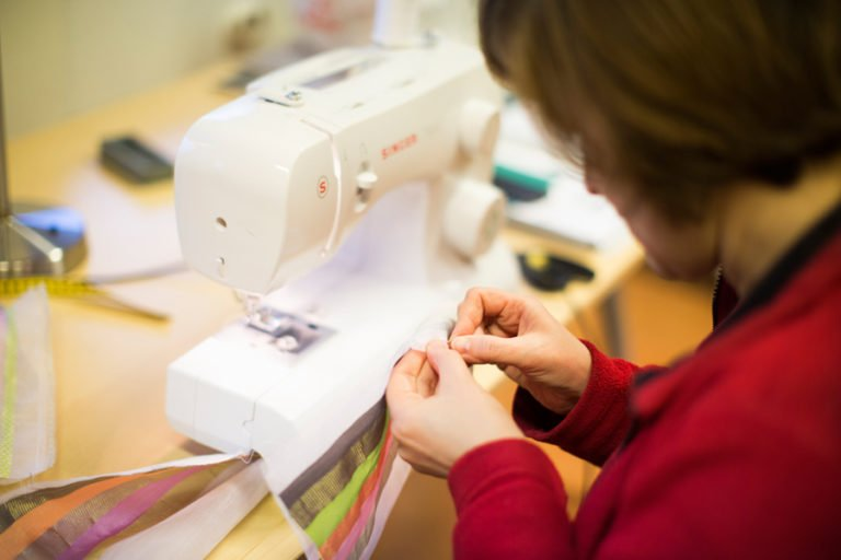 Nytida kvinna vid symaskin